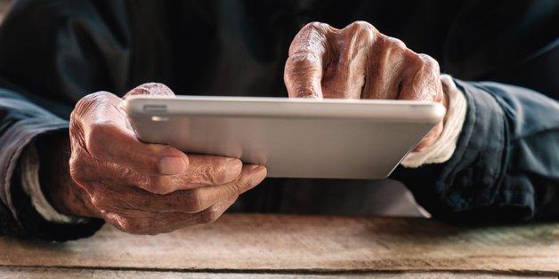 Ein alter Mann hält ein tablet in den Händen