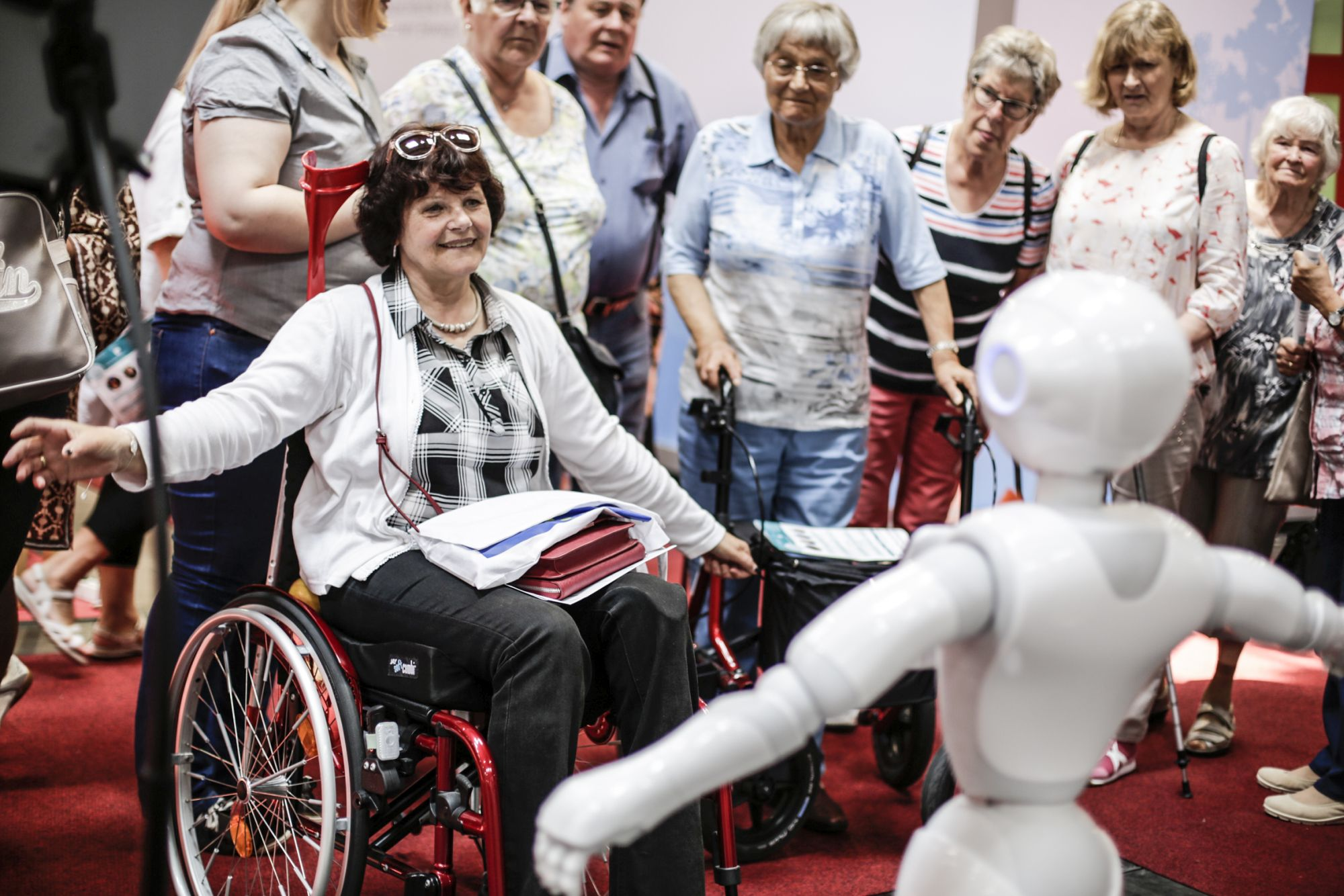 A woman sitting in a wheel chair looks at a robot while they both extend their arms to the side