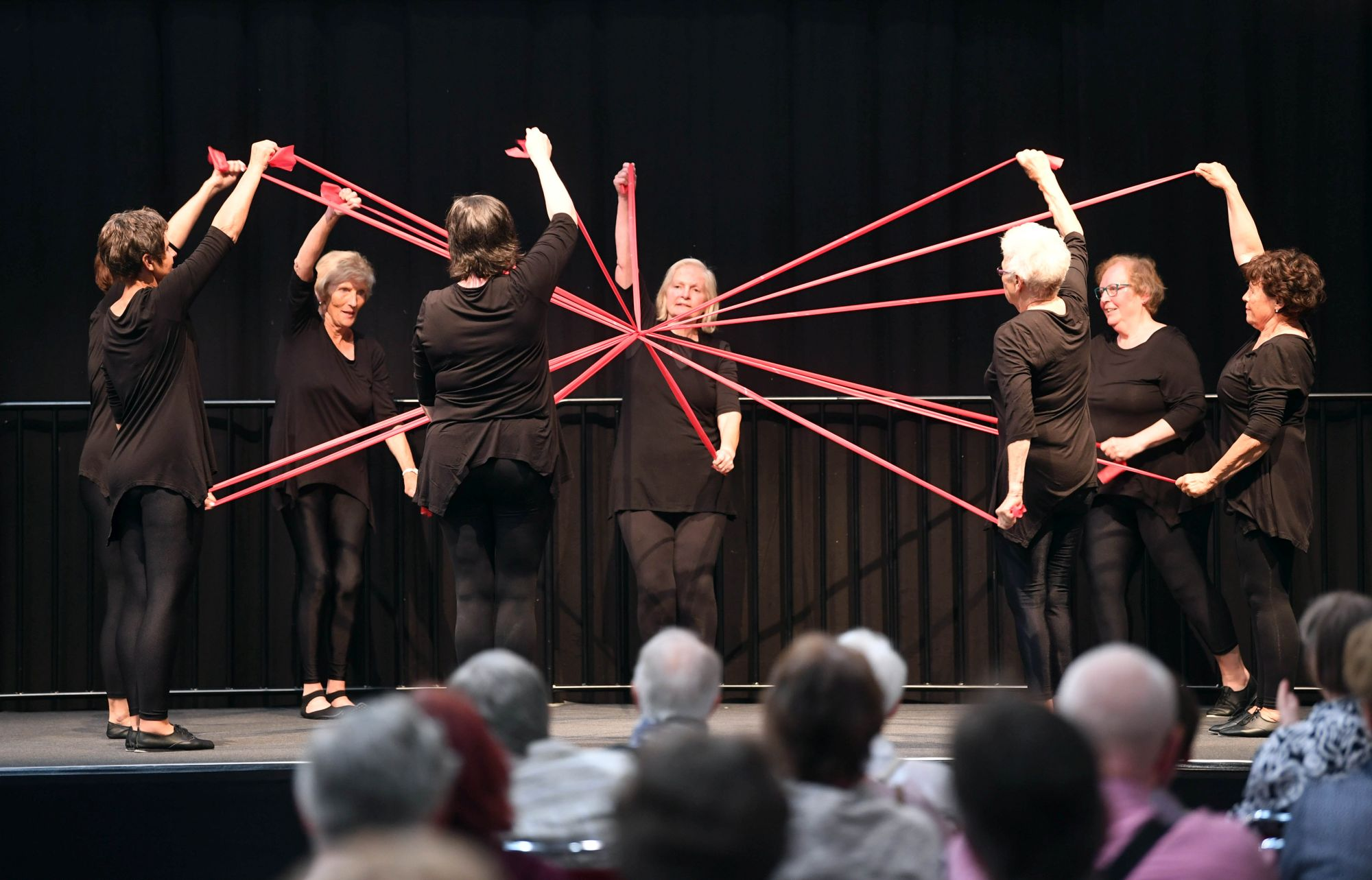 A group of women dressed in black stands in a circle on stage with a black curtain behind them. The women hold red ribbons which are building a knot in the centre of the circle