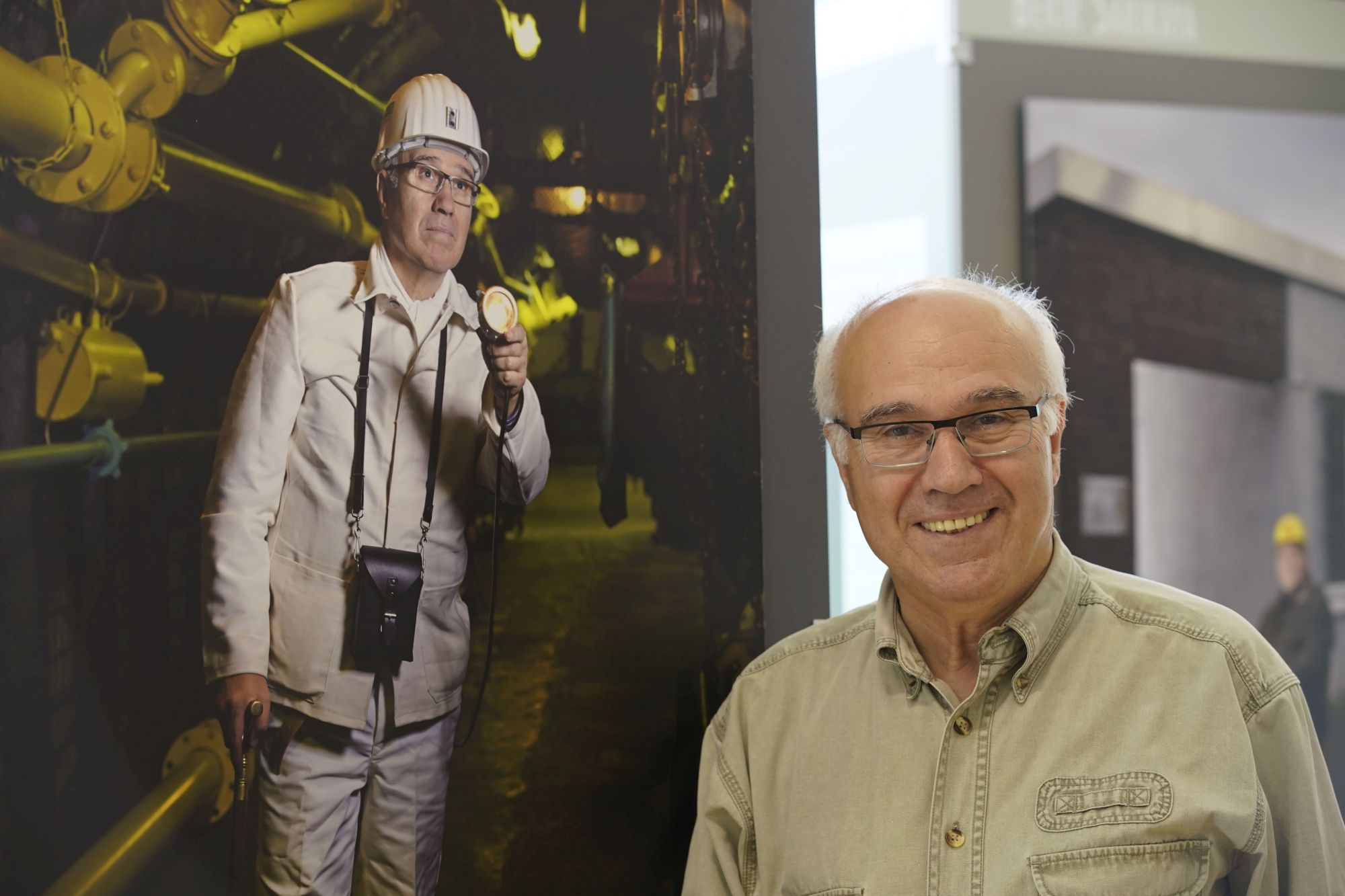 An older man stands in front of a life-size picture that shows himself as a miner. The photo is part of a travelling exhibition which was shown on the Senior Citizens Day